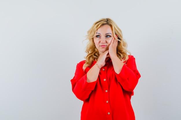 Blondynka opierając policzek pod ręką, pozowanie na kamery w czerwonej bluzce i ładnie wyglądający