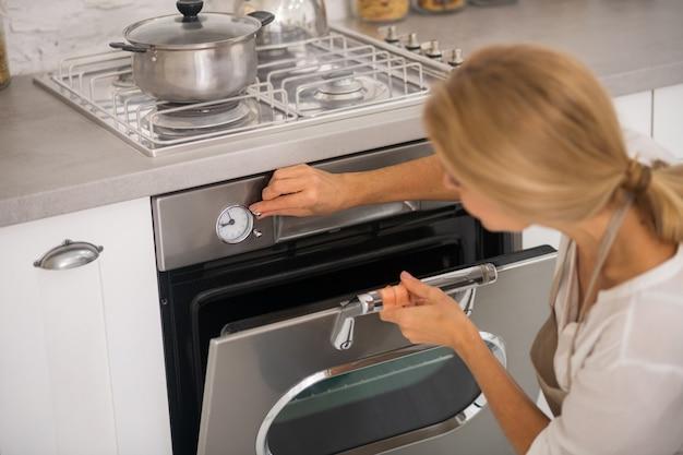 Blondynka, Otwierając Piekarnik W Kuchni Podczas Gotowania Obiadu Premium Zdjęcia