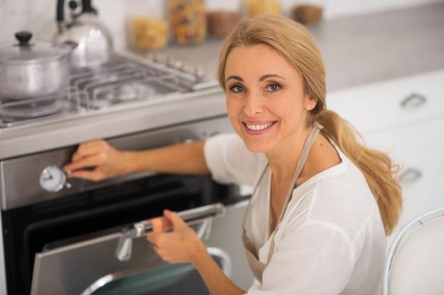 Blondynka, otwierając piekarnik w kuchni podczas gotowania obiadu