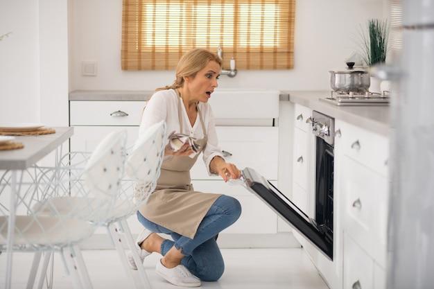 Blondynka otwierająca piekarnik w kuchni i wyglądająca na zszokowaną