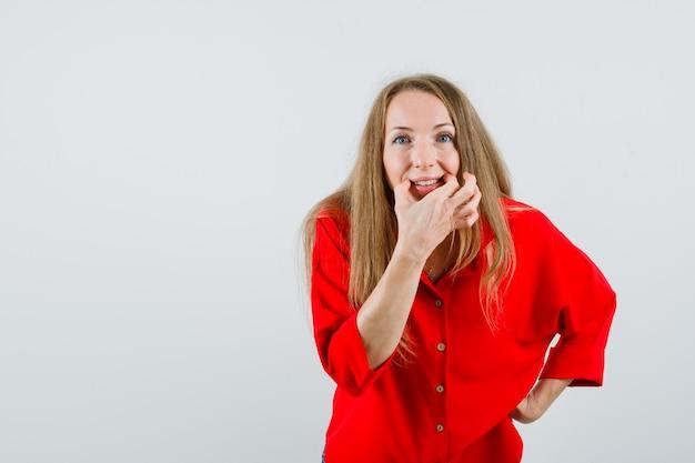 Blondynka otwierająca usta na gwizdek w czerwonej koszuli i wyglądająca wesoło