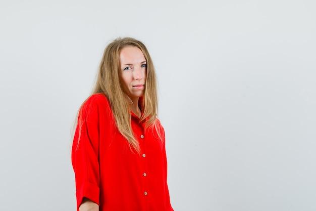 Blondynka patrząc na kamery w czerwonej koszuli i wątpiąca