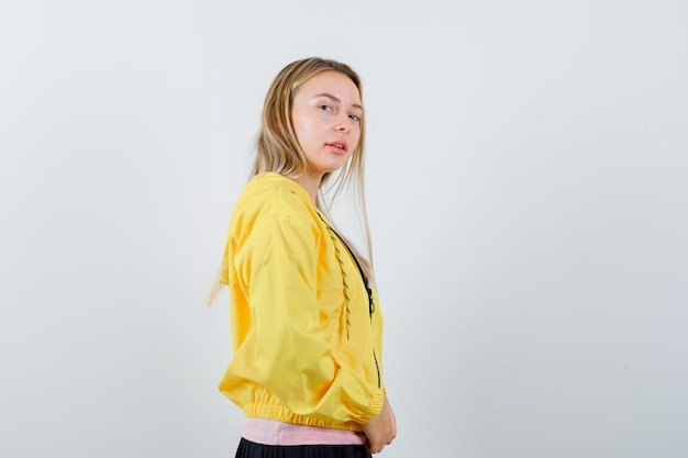 Blondynka, patrząc przez ramię, pozując do kamery w różowy t-shirt i żółtą kurtkę i pociągająco.