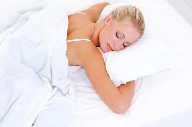 Blondynka piękna kobieta śpi w łóżku - strzelać pod dużym kątem
