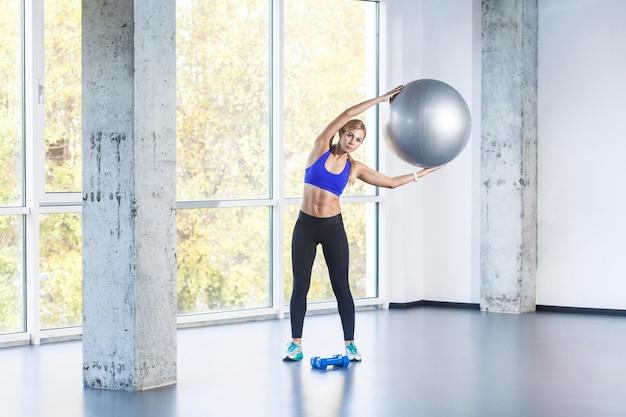 Blondynka po stronie pochylenia, trzymając fit piłkę. zdjęcia studyjne