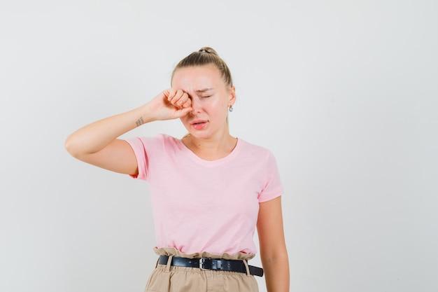 Blondynka pociera oko płacząc w t-shircie, spodniach i wygląda na obrażoną. przedni widok.