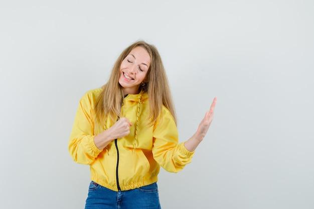 Blondynka podnosi rękę i zaciska pięść w kurtce, dżinsach i wygląda pewnie.