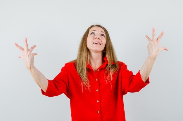 Blondynka podnosząca ręce, patrząc w górę w czerwonej koszuli i wyglądająca z nadzieją