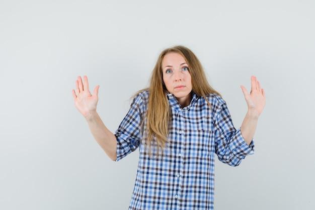Blondynka pokazująca dłonie w geście kapitulacji w koszuli i wyglądająca na przestraszoną