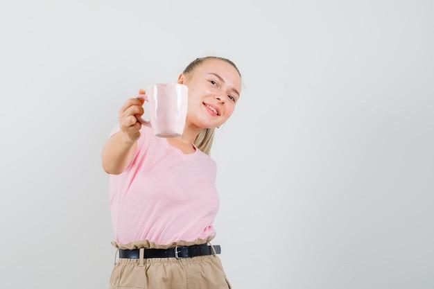 Blondynka pokazuje filiżankę napoju w t-shirt, spodnie i wygląda szczęśliwy. przedni widok.