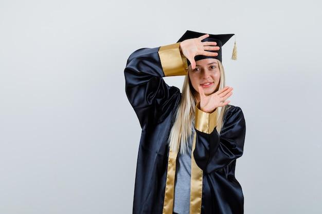 Blondynka pokazuje gest aparatu w sukni i czapce ukończenia szkoły i wygląda na szczęśliwą