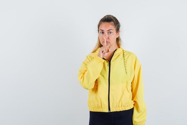 Blondynka pokazuje gest ciszy w żółtej bomberce i czarnych spodniach i wygląda poważnie