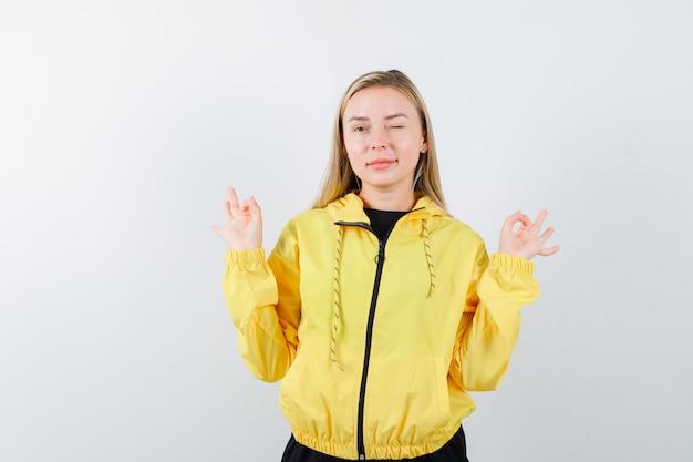 Blondynka pokazuje gest jogi, mruga okiem w dresie i wygląda pewnie. przedni widok.