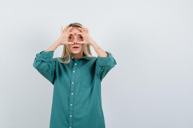 Blondynka pokazuje gest lornetki w zielonej bluzce i patrząc skupiony.