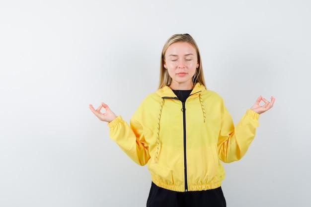 Blondynka pokazuje gest medytacji z zamkniętymi oczami w dresie i wygląda na zrelaksowanego. przedni widok.