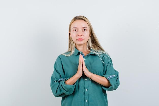 Blondynka pokazuje gest namaste w zielonej bluzce i promienny wygląd.