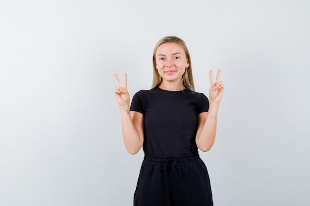 Blondynka pokazuje gest zwycięstwa w czarnej sukience i szuka szczęścia. przedni widok.