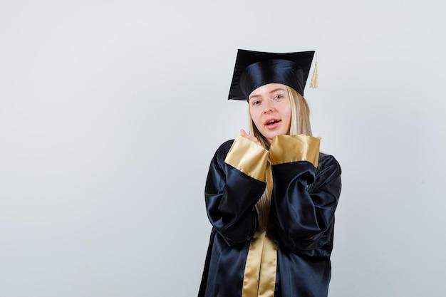 Blondynka pokazuje gest zwycięzcy w sukni i czapce ukończenia szkoły i wygląda na szczęśliwą.
