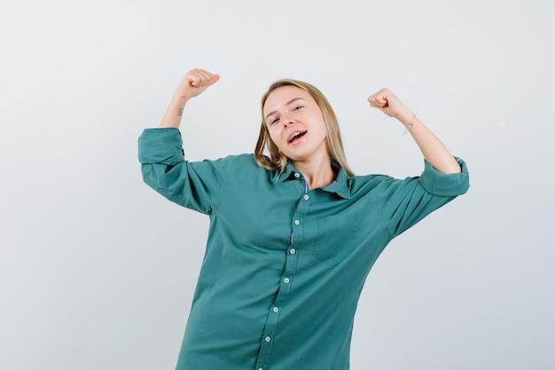 Blondynka pokazuje gest zwycięzcy w zielonej bluzce i wygląda na szczęśliwą