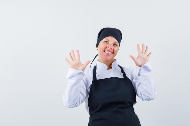 Blondynka pokazuje gesty stop w czarnym mundurze kucharza i wygląda ładnie.