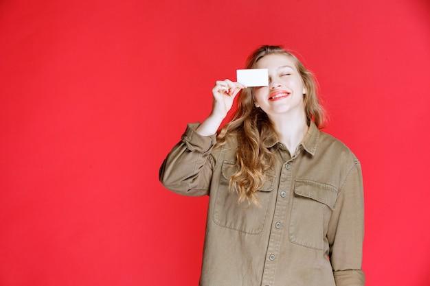 Blondynka pokazuje jej wizytówkę i sieci.