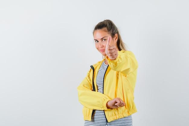 Blondynka pokazuje kciuk w żółtej bomberce i koszuli w paski i wygląda pewnie