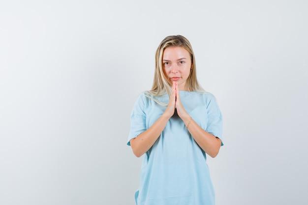Blondynka pokazuje namaste gest w niebieskiej koszulce i wygląda ładnie. przedni widok.