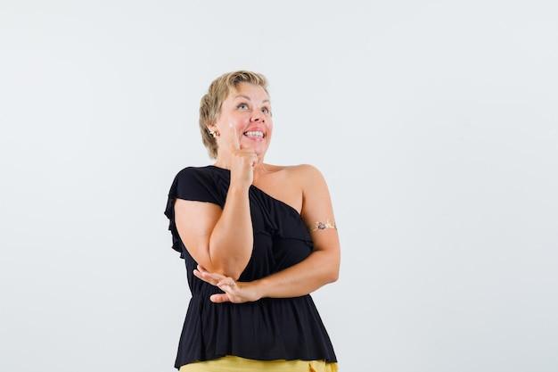 Blondynka pokazuje nowy pomysł gest w czarnej bluzce i wygląda wesoło