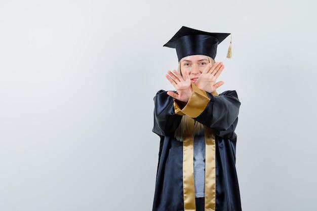 Blondynka pokazuje ograniczenie lub gest x w sukni i czapce ukończenia szkoły i wygląda poważnie