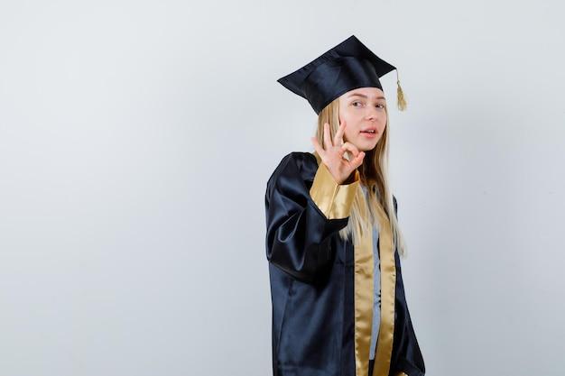 Blondynka pokazuje ok znak w sukni i czapce ukończenia szkoły i wygląda na szczęśliwą