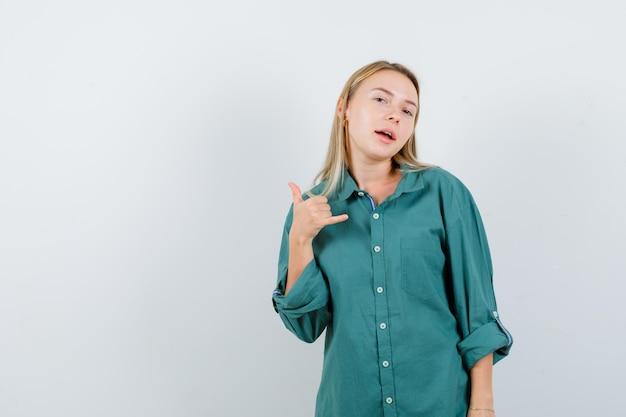 Blondynka pokazuje zadzwoń do mnie gest w zielonej bluzce i wygląda na szczęśliwą.