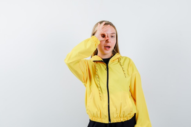 Blondynka pokazuje znak ok na oku w dresie i wygląda na zdumioną, widok z przodu.