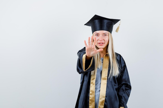Blondynka pokazuje znak stop w ukończeniu suknia i czapka i patrząc szczęśliwy.