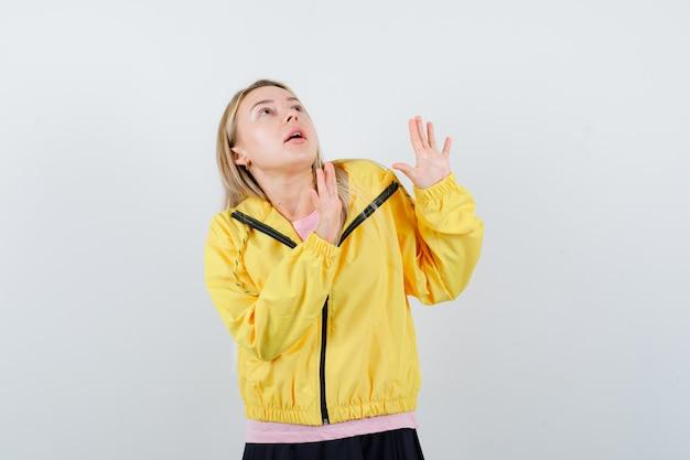 Blondynka pokazuje znaki stop w różowej koszulce i żółtej kurtce i wygląda na przestraszoną