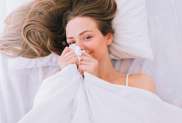 Blondynka pozuje na łóżku