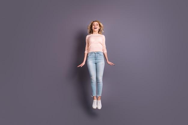 Blondynka pozuje w swetrze na fioletowej ścianie