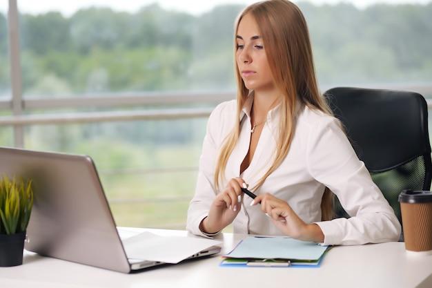 Blondynka pracuje na komputerze, kobieta biznesu w biurze