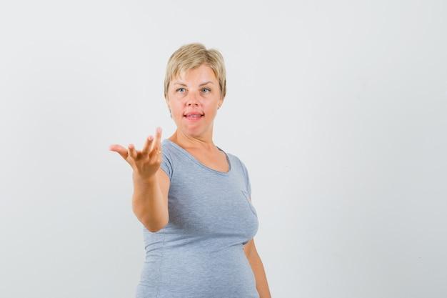 Blondynka próbuje wyjaśnić coś w jasnoniebieskiej koszulce i wygląda poważnie. przedni widok.