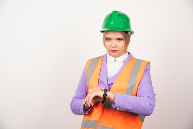 Blondynka przemysłowa pracownik trzyma zegarek na białym.