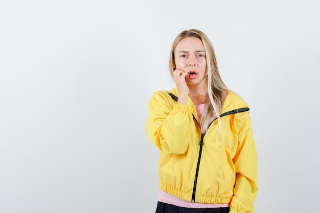 Blondynka przykłada rękę do ust, trzymając szeroko otwarte usta w różowej koszulce i żółtej kurtce i wygląda na zaskoczoną