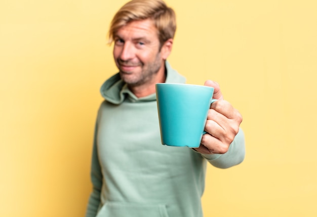 Blondynka przystojny dorosły mężczyzna trzyma filiżankę kawy