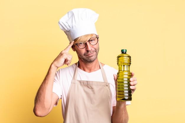 Blondynka przystojny kucharz dorosły mężczyzna trzyma butelkę oliwy z oliwek