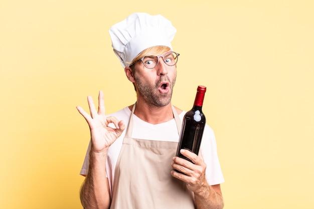 Blondynka przystojny kucharz dorosły mężczyzna trzyma butelkę wina