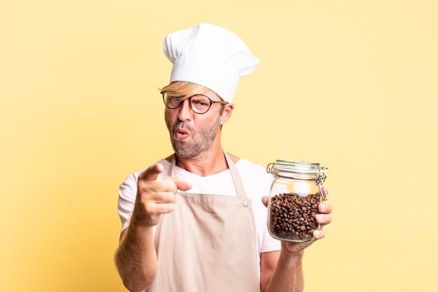 Blondynka przystojny kucharz dorosły mężczyzna trzyma butelkę ziaren kawy