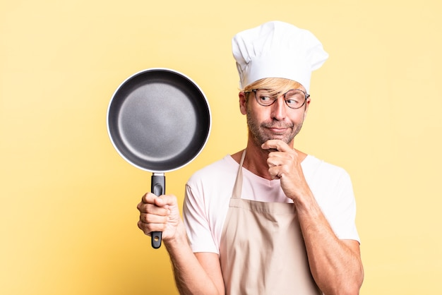 Blondynka przystojny kucharz dorosły mężczyzna trzyma patelnię