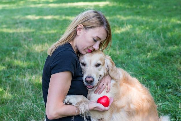 Blondynka przytula pies retriever, trzymając w ręku czerwone serce. pojęcie kochających zwierząt.