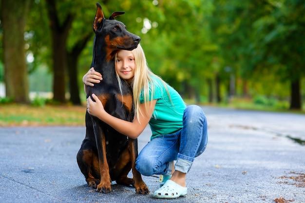 Blondynka przytula swojego ukochanego psa dobermana w letnim parku