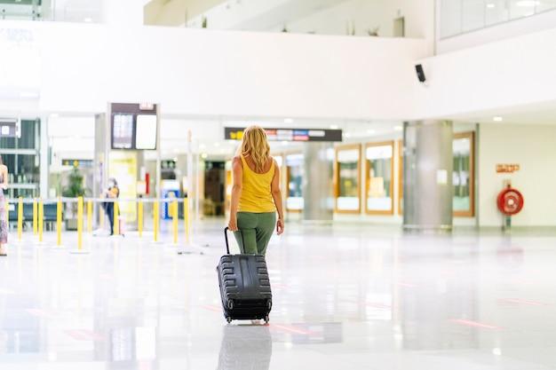 Blondynka rasy kaukaskiej w żółtej koszuli spacerującej po lotnisku z bagażem