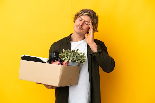 Blondynka robi ruch, podnosząc pudełko pełne rzeczy na białym tle