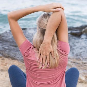 Blondynka rozciągający się na plaży